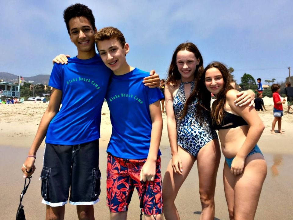Four teenage campers, two boys and two girls, hanging out together on the beach at Aloha Beach Camp.