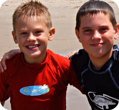 Two boys standing together at Aloha Beach Camp with arms around each other. One is wearing a red Aloha Beach Camp rash guard.