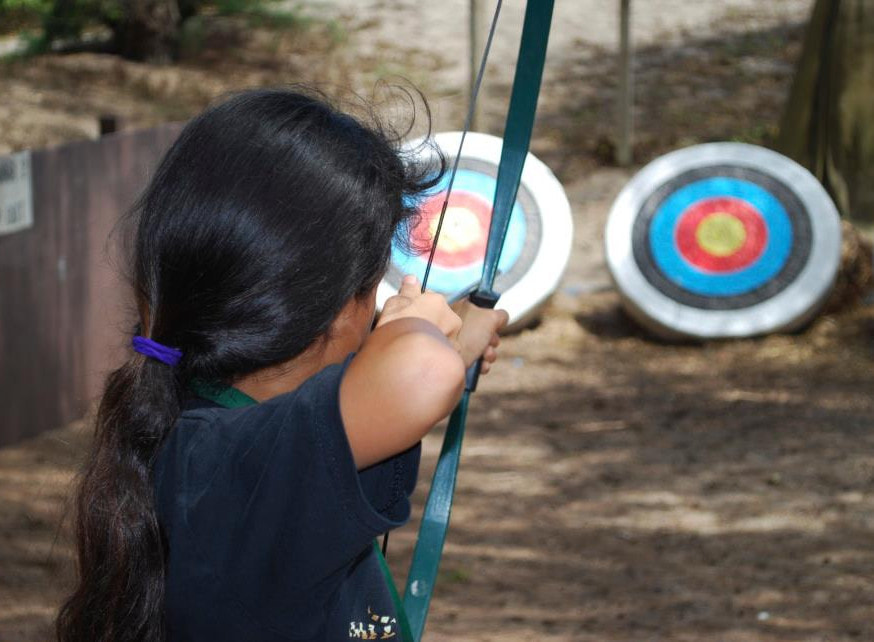 Girl doing archery at Aloha Beach Camp's Hawaii overnight program.