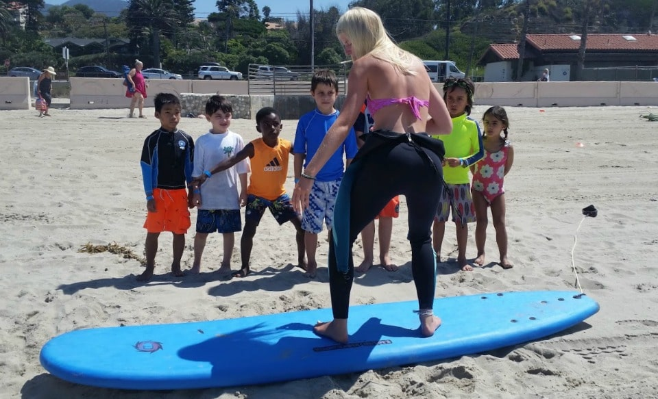Surf camp director Aurora Eagles giving a surfing lesson on the sand to a group of young Aloha Beach Camp campers.