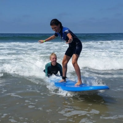 Camp counselor providing surfing instruction in the ocean to a teenage Aloha Beach Camp female camper.