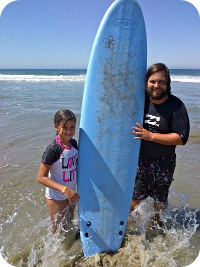 Surf camp director Matt Duda and a little girl he just taught how to surf standing in the ocean together holding a surfboard vertically between them.