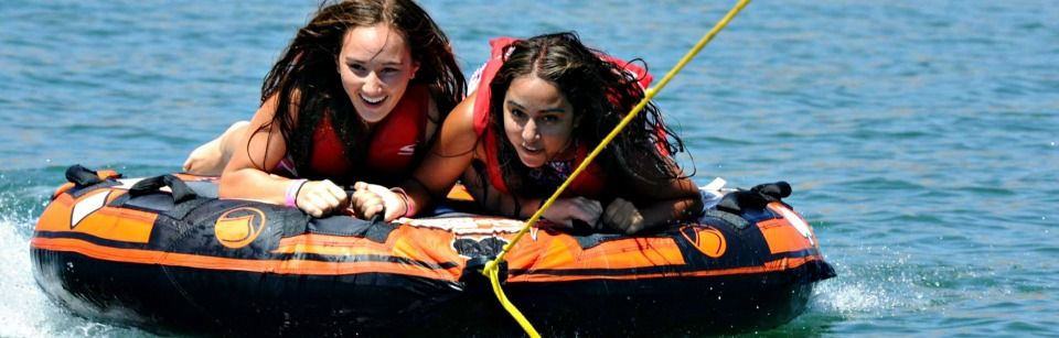 Two teenage girls tubing at Aloha Beach Camp.