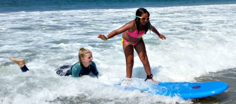 11 year old girl learning to surf at Aloha Beach Camp's Billabong Surf Camp at Zuma Beach in Malibu while her female surfing instructor holds the back of her board in the ocean to provide extra guidance, balance and support.