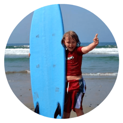 Boy standing on beach holding a surfboard giving