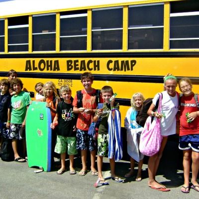 Campers stading in front of an Aloha Beach Camp Summer Camp bus.
