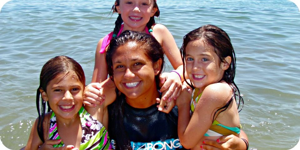 Aloha Beach Camp counselor Taryn Wahl holding two female campers in her arms as another sits on her shoulder as they post for a group photo in the ocean at Paradise Cove, Malibu.