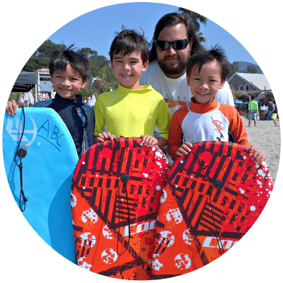Three boys holding boogie boards standing on the beach with Aloha Beach Camp day camp director Matt Duda.