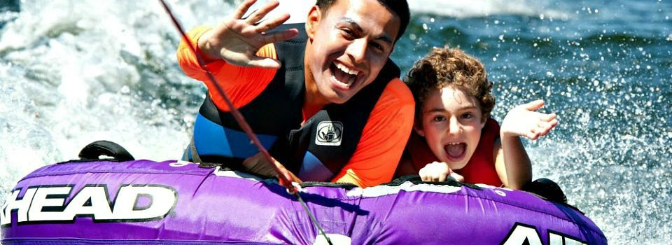 Counselor and camper tubing at Castic Lake. They are smiling, waving and having a blast!