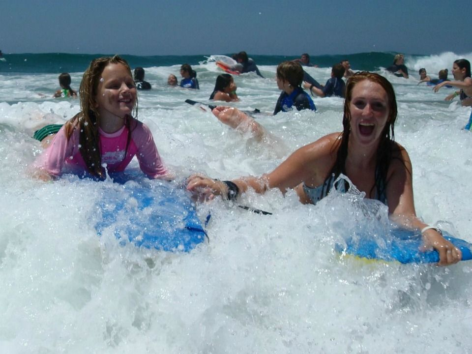 Female camper from Tarzana, wearing a pink rash guard, and her camp counselor smiling and holding hands while boogie boarding together in the ocean at Aloha Beach Camp.