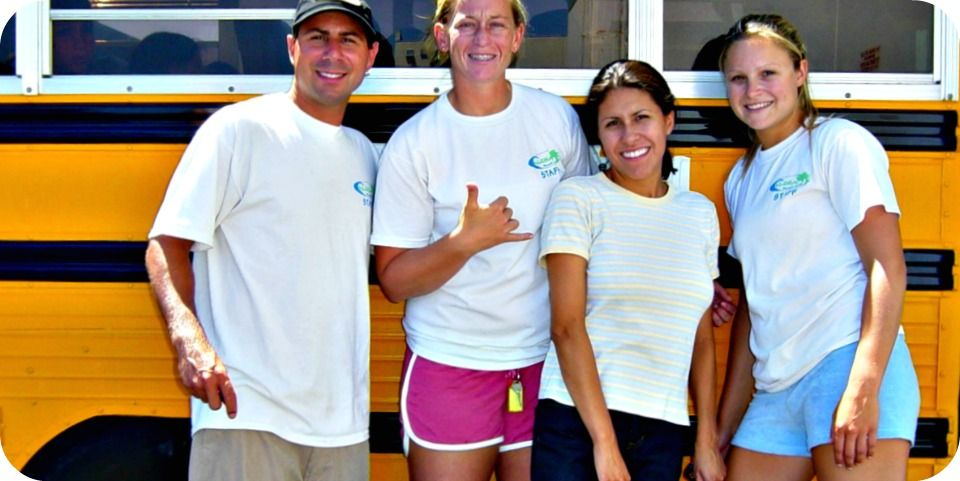 Four Aloha Beach Camp counselors from Conejo Valley standing in front of an Aloha Beach Camp summer camp bus.