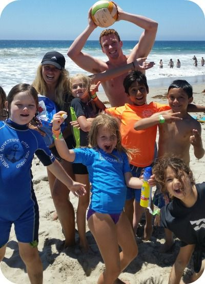 Two Aloha Beach Camp Counselors standing together with a group of 6 boys and girls at Zuma Beach.