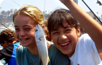 Two High Action camper girls, each 13 years old, standing on the Santa Monica Pier smiling while proudling showing off the small fish they caught at Aloha Beach Camp's fishing derby activity day.