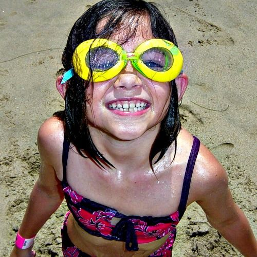 Young Keiki Camper girl wearing a pink bathing suit and bright yellow goggles standing on the sand at Aloha Beach Camp.