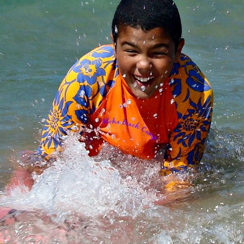 Happy smiling boy in bright orange rash guard with Aloha Beach Camp logo on the front boogie boarding at Aloha Beach Camp