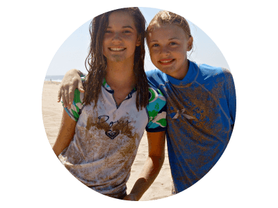 Two female teenage campers from Beverly Hills covered in sand and smiling at Aloha Beach Camp Day Camp. These girls are just two of dozens and dozens of happy campers from the Beverly HIlls are who enjoy Aloha Beach Camp program each summer.