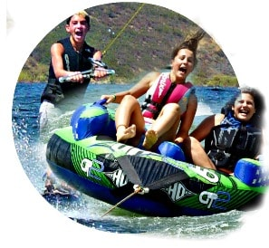 Three High Action Campers, two girls and one boy, laughing and smiling while enjoing Aloha Beach Camp's wakeboarding and innertubing activities at Castaic Lake.