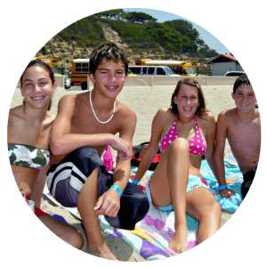 Four teenagers, two boys and two girls, sittign on their towels and hanging out together on the beach at Aloha Beach Camp's High Action summer day camp program in Malibu.