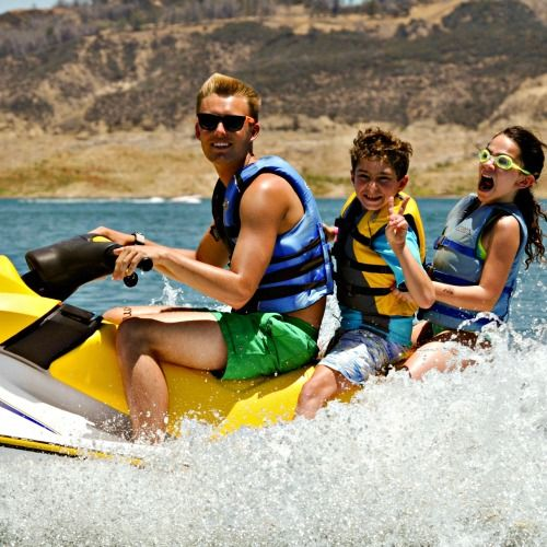 Two campers screaming with joy as their camp counselor gives them an exciting jet ski ride accross Castaic Lake at Aloha Beach Camp.