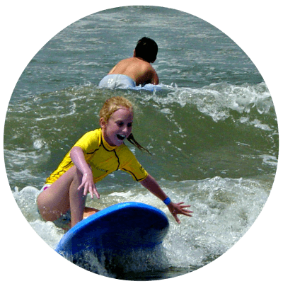 Girl at summer camp surfing on a blue surfboard catching a good wave.