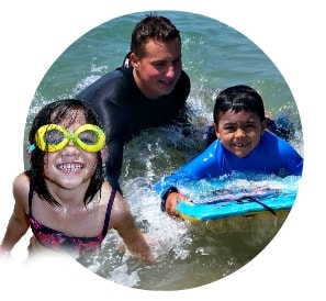Two happy Keiki Campers, one 5 year old girl and a 6 year old boy, swim and boogie board together in the ocean as their Camp Counselor, Jeremy Polon, looks on.