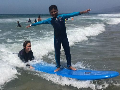 Camper from the Pacific Palisades taking a surfing lesson from his Aloha Beach Camp surf instructor.