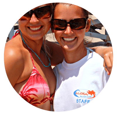Two female Aloha Beach Camp counselors with arms around each other on the beach
