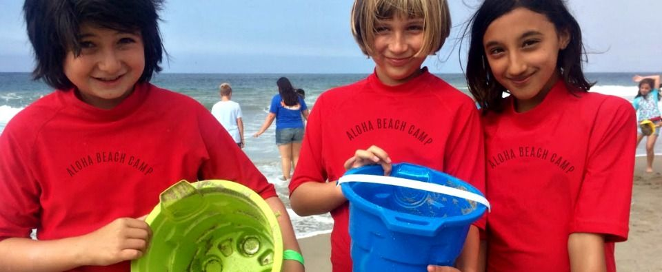 Three Aloha Beach Camp kids from Santa Monica playing with beach toys and sand buckets, standing side-by-side at Zuma Beach, each wearing red Aloha Beach Camp logo-emblazoned rash guards swim shirts.