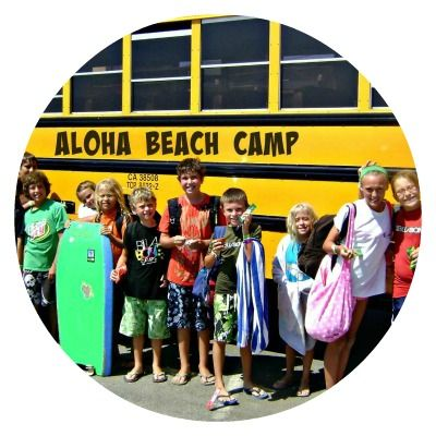 Group of Aloha Beach Camp kids from Thousand Oaks standing in front of their yellow summer camp bus.