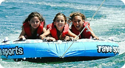 Three female campers from the Conejo Valley enjoying a tubing ride at Aloha Beach Camp.