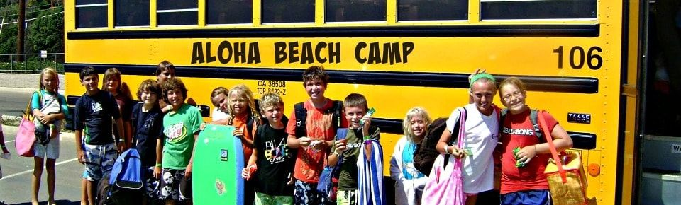 Campers pose with their beach towels, boogie boards and other camp gear in front of an Aloha Beach Camp summer camp bus.